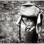 A little girl hold her school bag above her head during rains