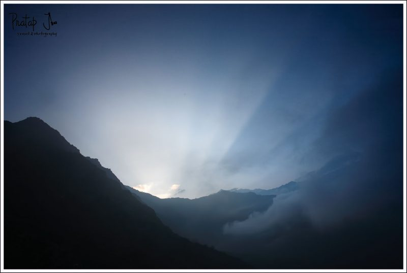 The sun rises from behind the mountains in the Himalayas on the Kuari Pass trek