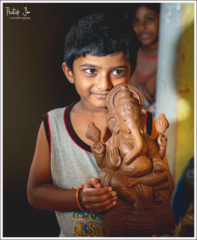 Boy holding a clay Ganesha