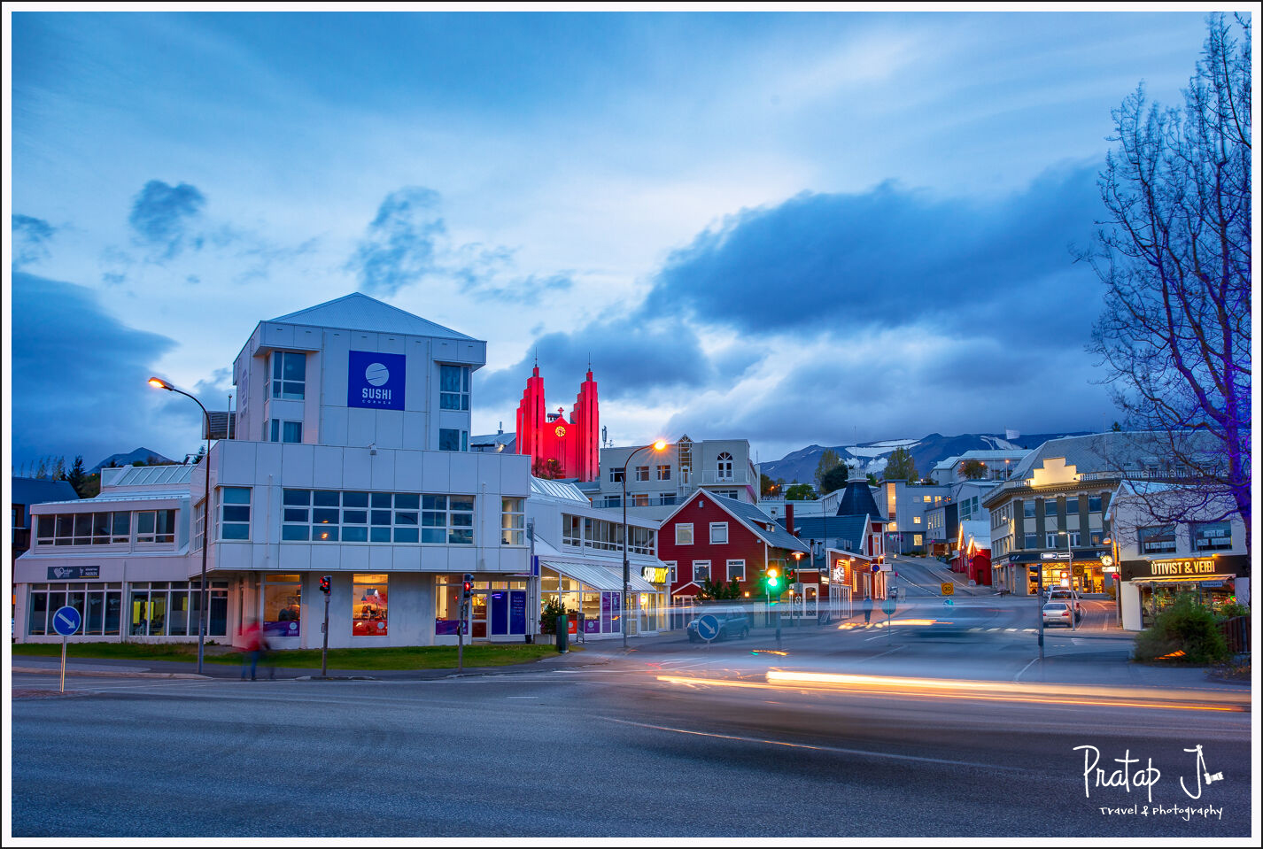 A traffic junction of Akureyri with colours buildings and he mountain the background