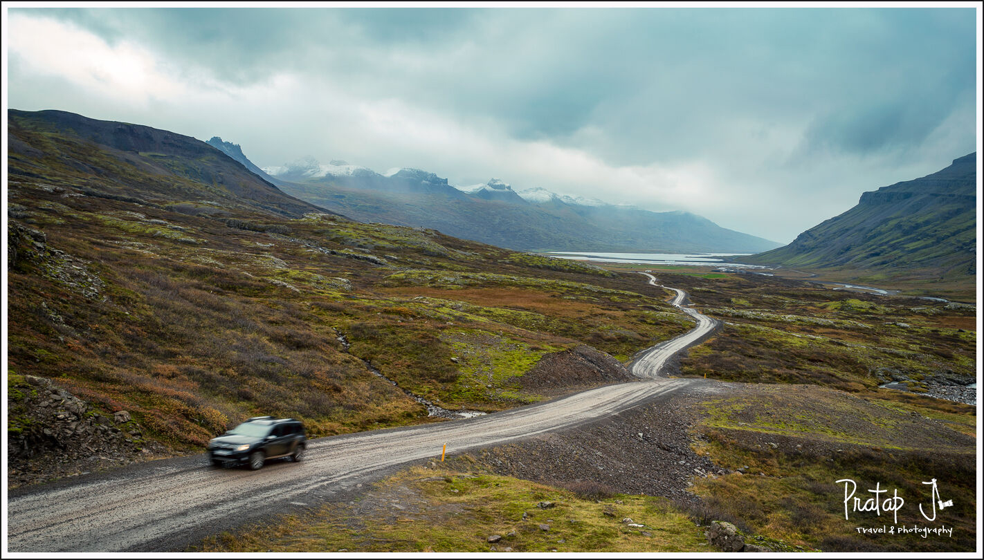 A winding road with a car on it and distant snow clad mountains in the East Fjords of Iceland